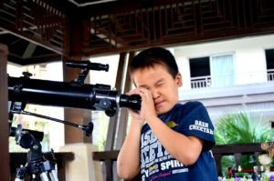 Ein Teleskop für Kinder, das einen Junge an einem Teleskop zeigt